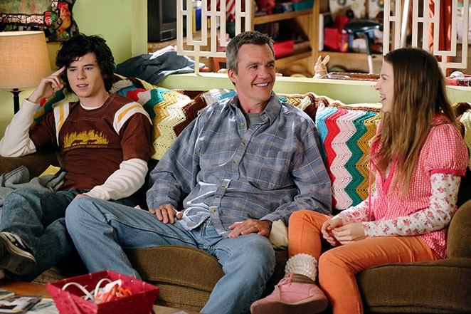 Two kids sit next to their dad on a couch