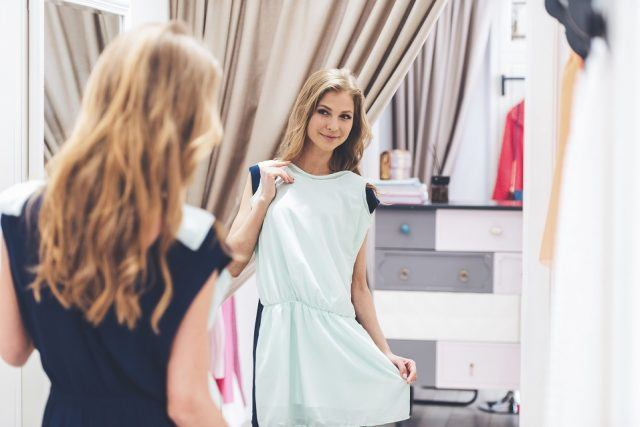 beautiful young woman trying on dress and looking at her reflection