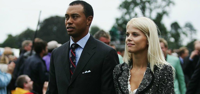 Tiger and Elin Woods are standing next to each other.