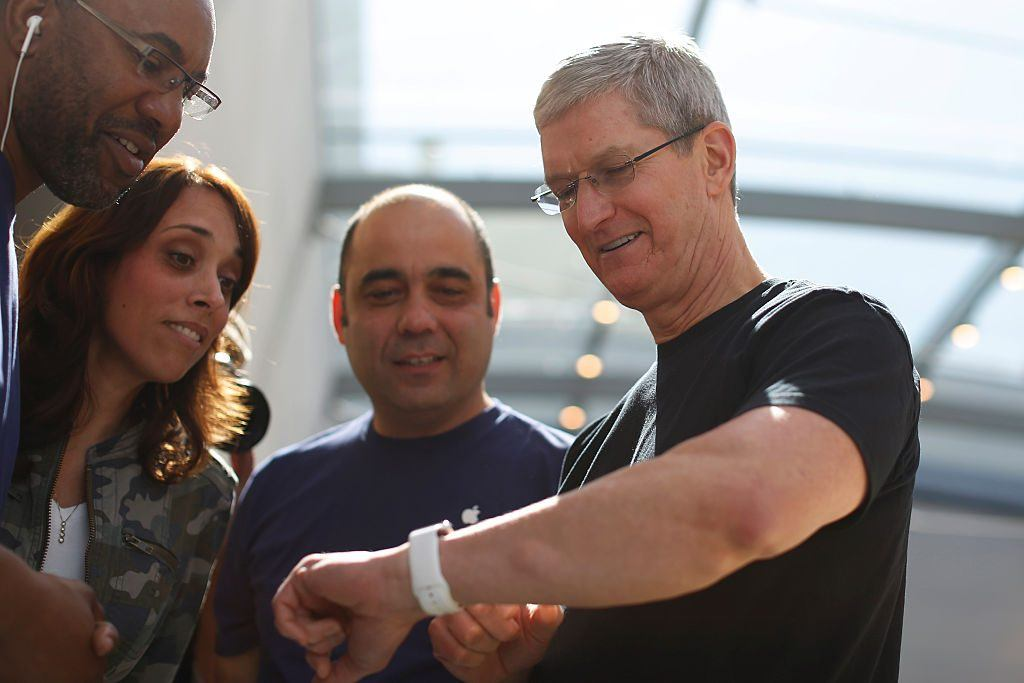 Apple CEO Tim Cook displays his personal Apple Watch to customers at an Apple Store