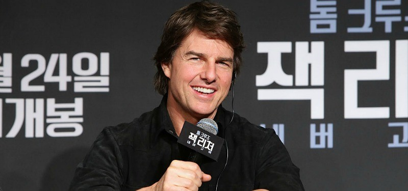 Tom Cruise holding a microphone at a press conference.