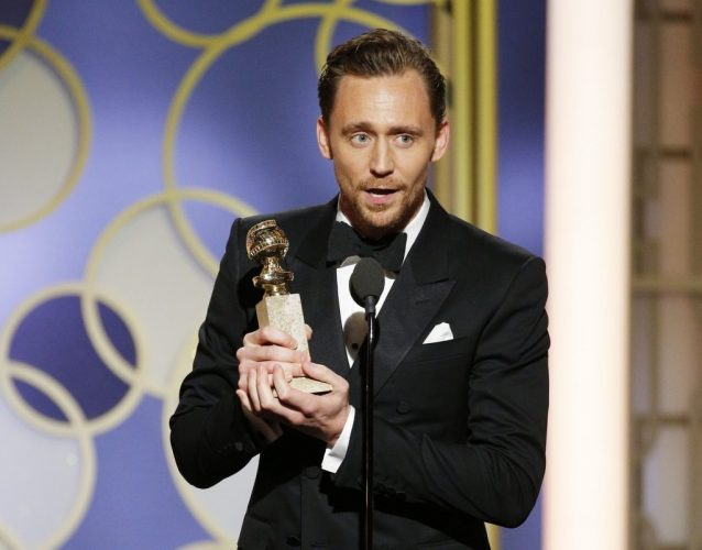 Tom Hiddleston stands holding an award while giving a speech onstage.