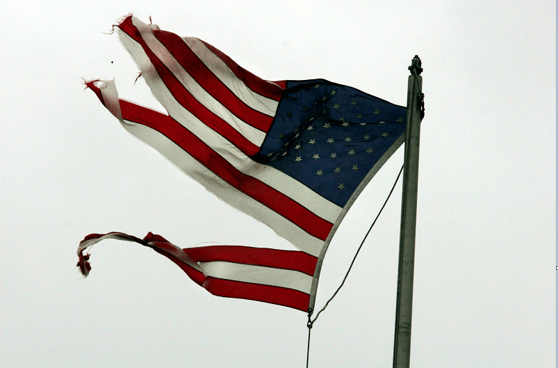 A tattered American flag signifies the broken American dream.
