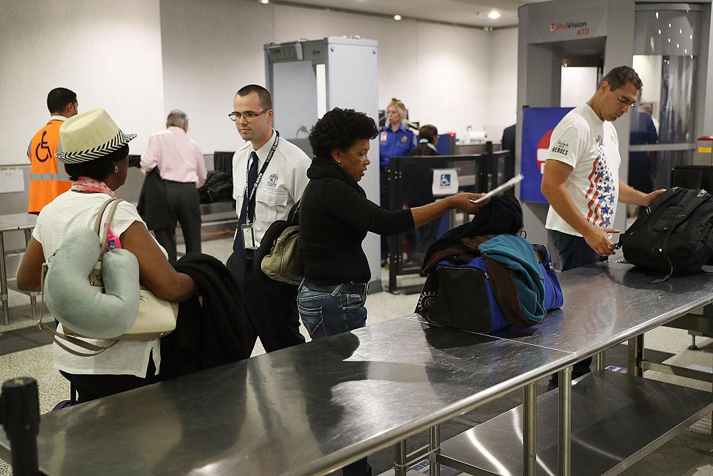 Travelers go through the TSA PreCheck security point at Miami International Airport