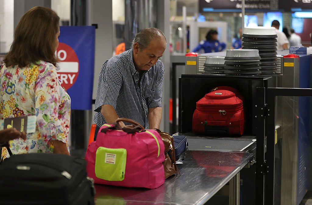 Travelers go through the TSA PreCheck security point at Miami International Airport