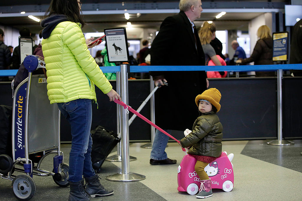 A girl sits on her toy as travelers walk though the TSA security line at O'Hare International Airport