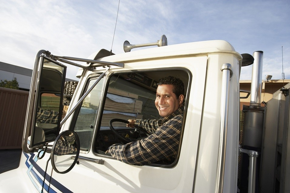 A truck driver smiles from the cab of his truck.