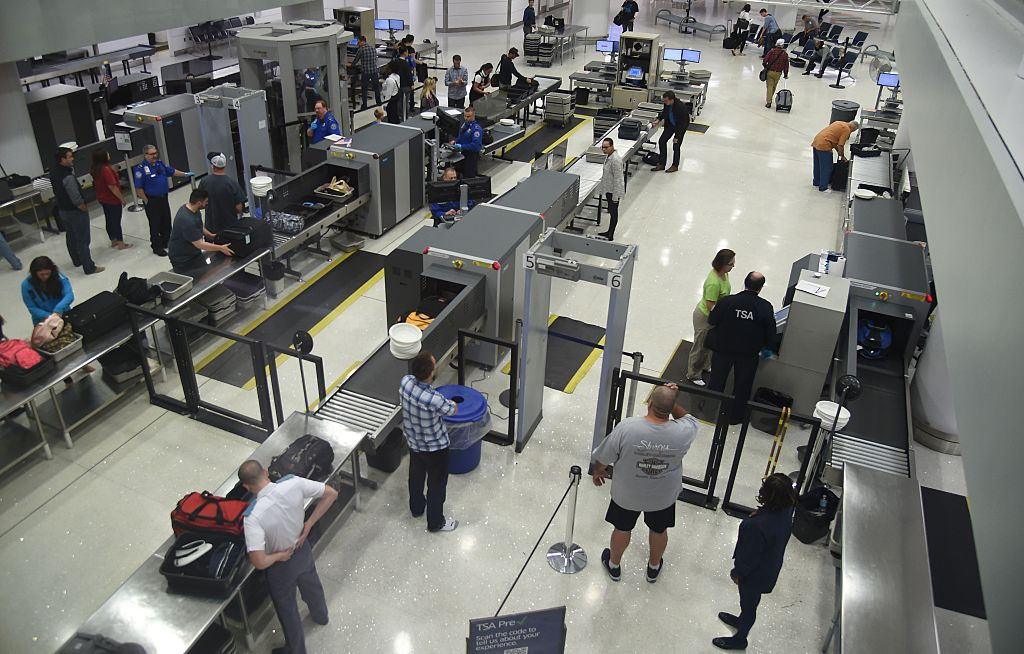 US Transportation Security Administration (TSA) officers inspect airline passengers