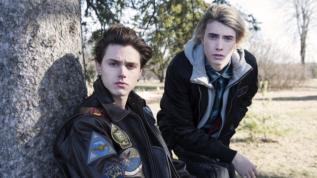 Tyler Young as Philip Shea and James Paxton as Lukas Waldenbeck sit in front of a tree in USA's Eyewitness