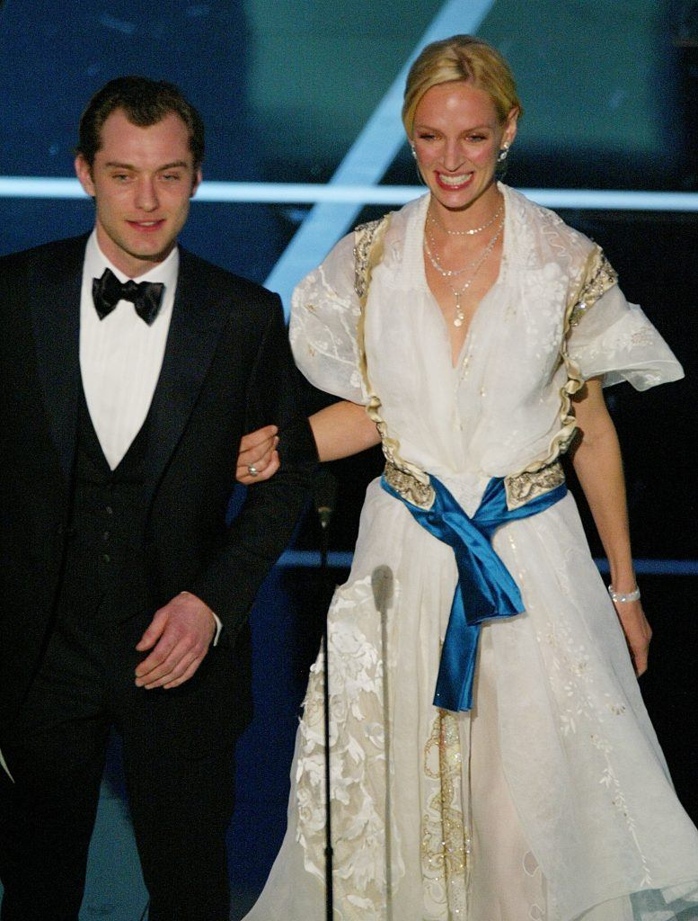 Actor Jude Law and actress Uma Thurman who is wearing a makeshift white dress with a blue sash
