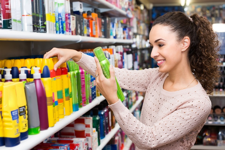 woman buying hairspray and shampoo at the store