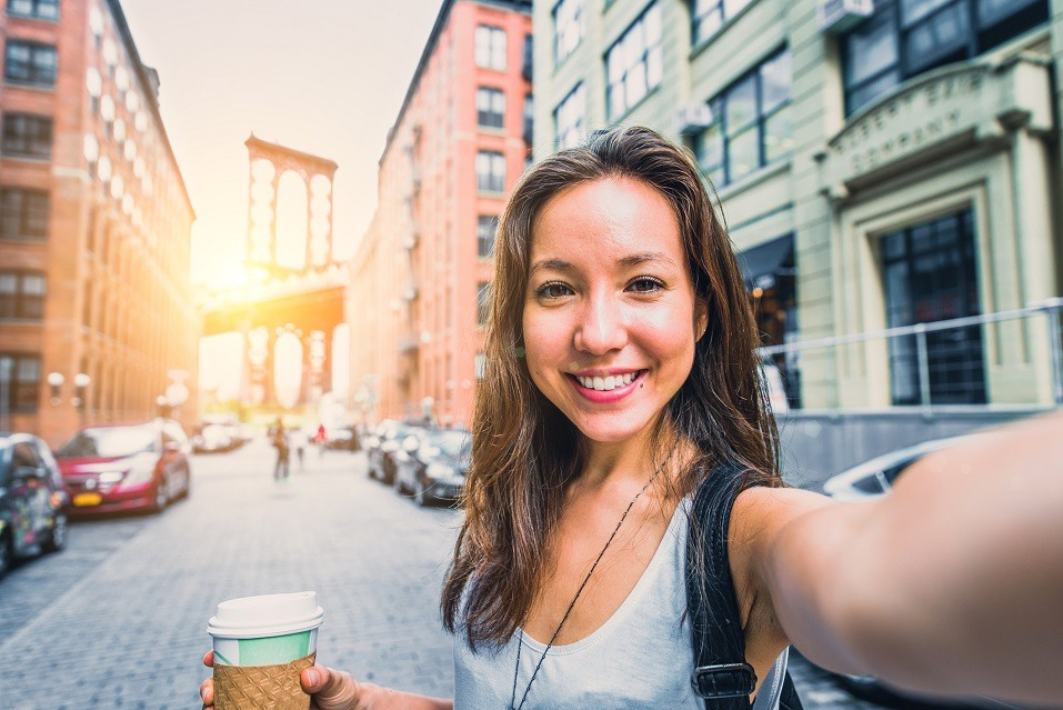 Woman taking selfie and writing selfie captions for Instagram