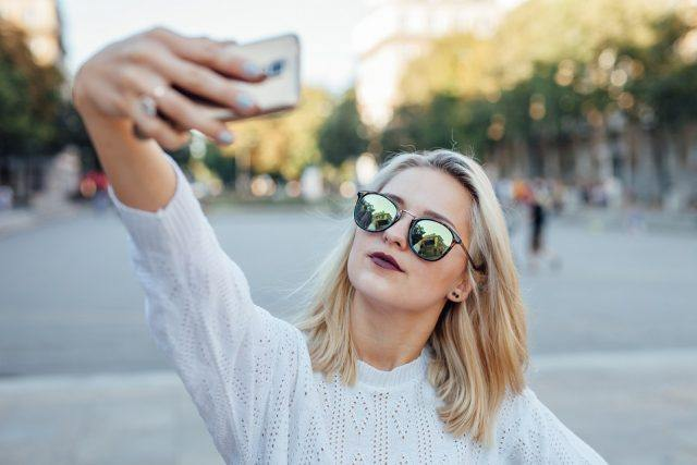 A young woman is taking a selfie.