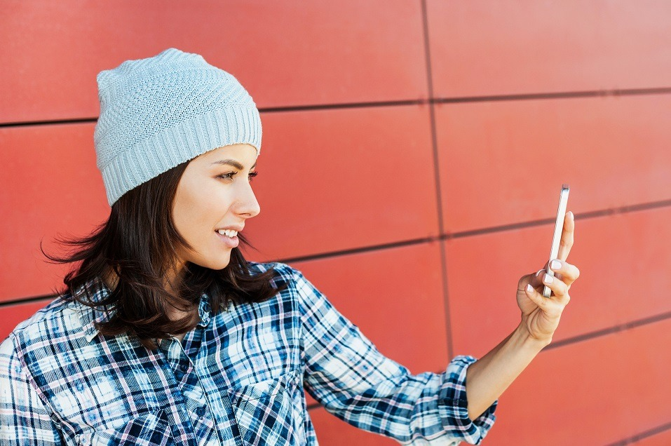 woman taking a selfie on a city street and writing selfie captions for Instagram