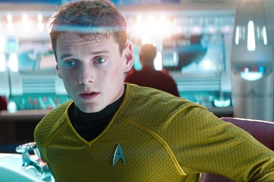 Anton Yelchin sits in a chair and looks off camera in Star Trek