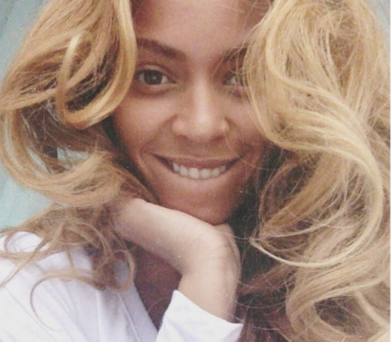 Beyoncé is biting her lip and has her blonde hair falling in front of her makeup free face.