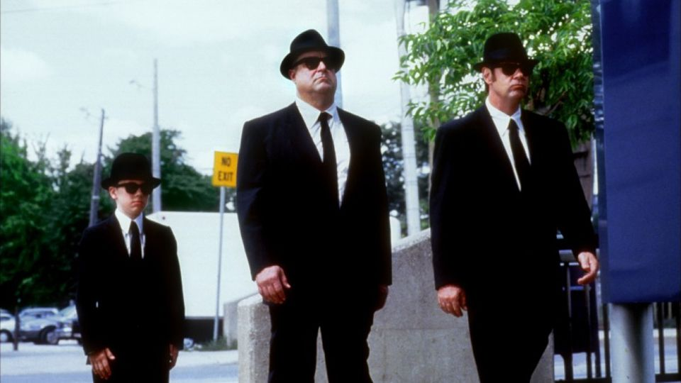 John Goodman and Dan Akroyd wearing black suits, fedoras, and sunglasses