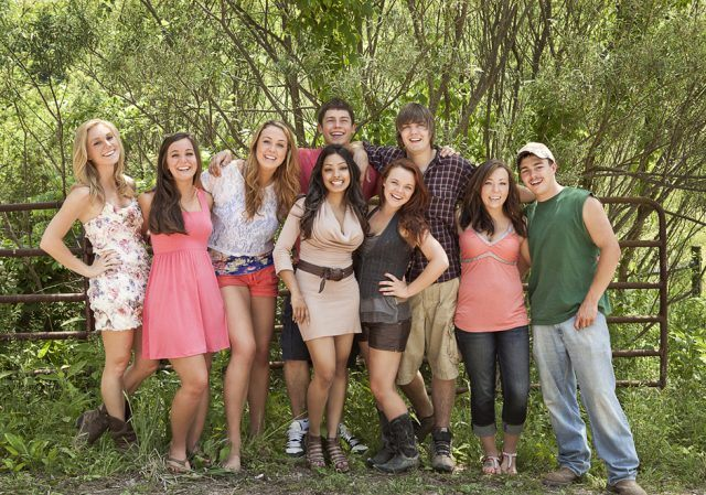 The cast of MTV's 'Buckwild' poses together for a photo in front of a metal fence