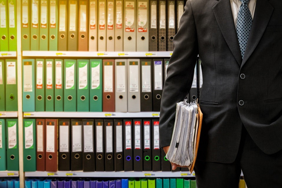 Businessman standing in front of a wall of binders