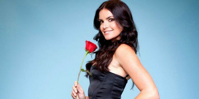 Courtney Robertson posing with a red rose.