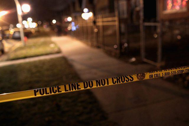 A yellow crime tape on a sidewalk.