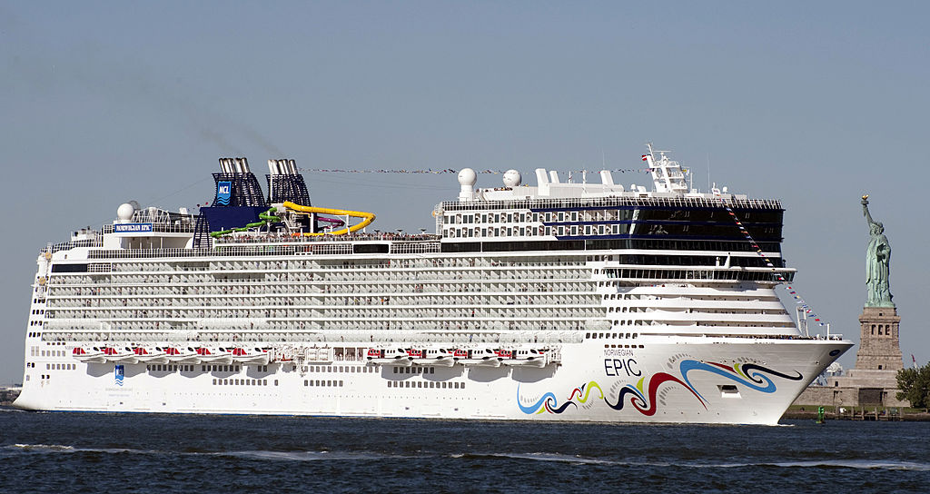 The Norwegian Epic, one of the top 10 largest cruise ships in the world, dwarfs the Statue of Liberty as it sails past.