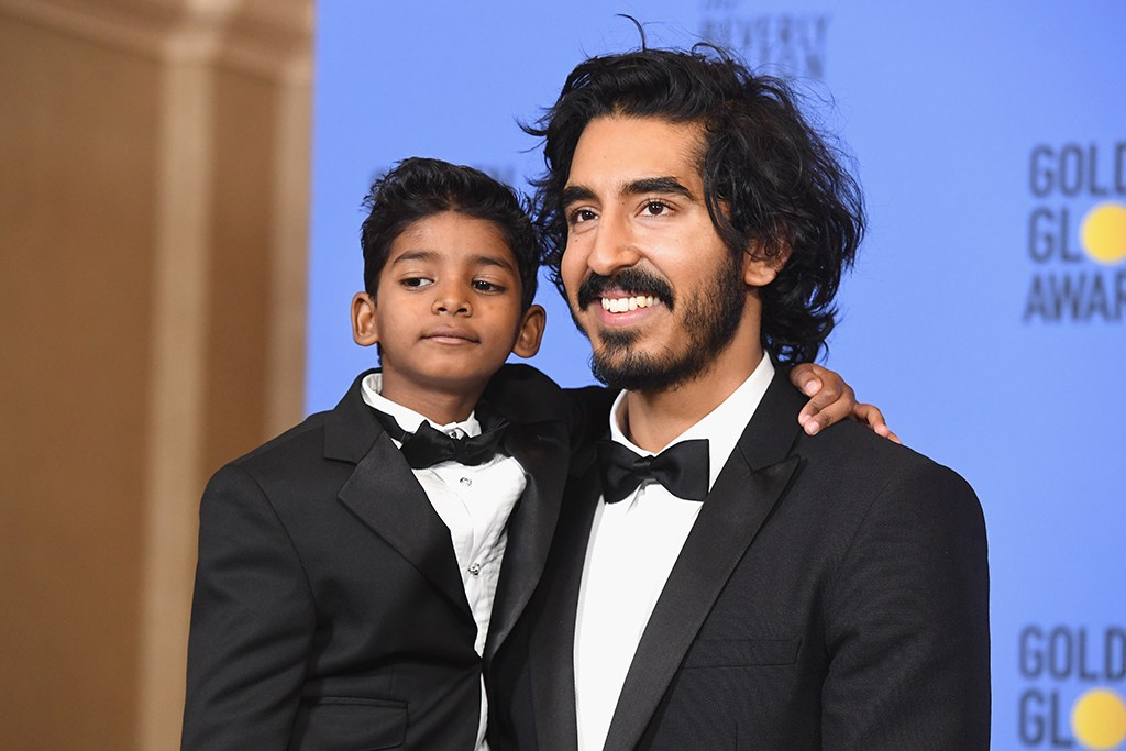 Dev Patel in a tux holding Sunny Pawar