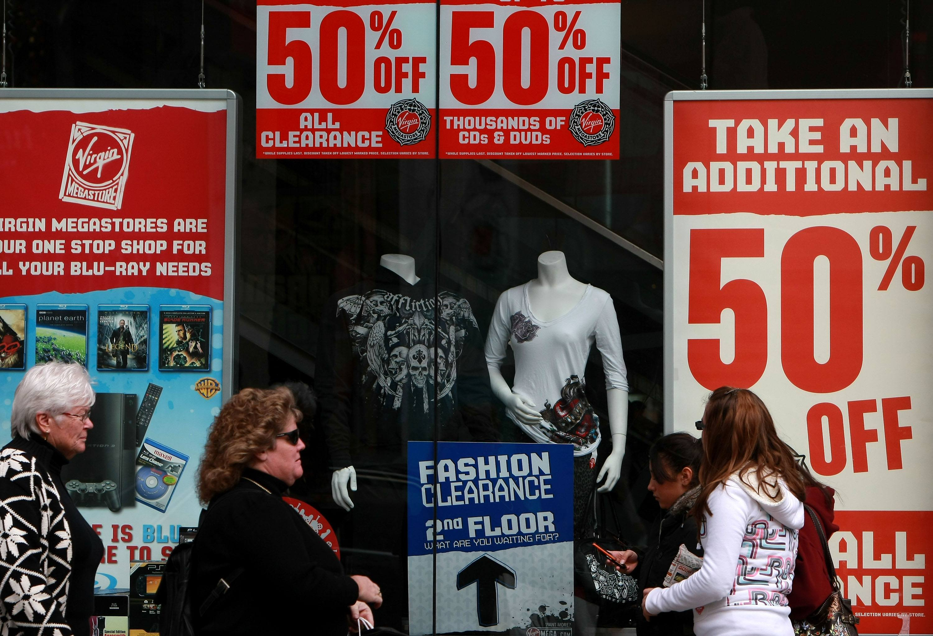 Pedestrians walk by sale signs looking for deals and the best ways of saving money in the retail sector