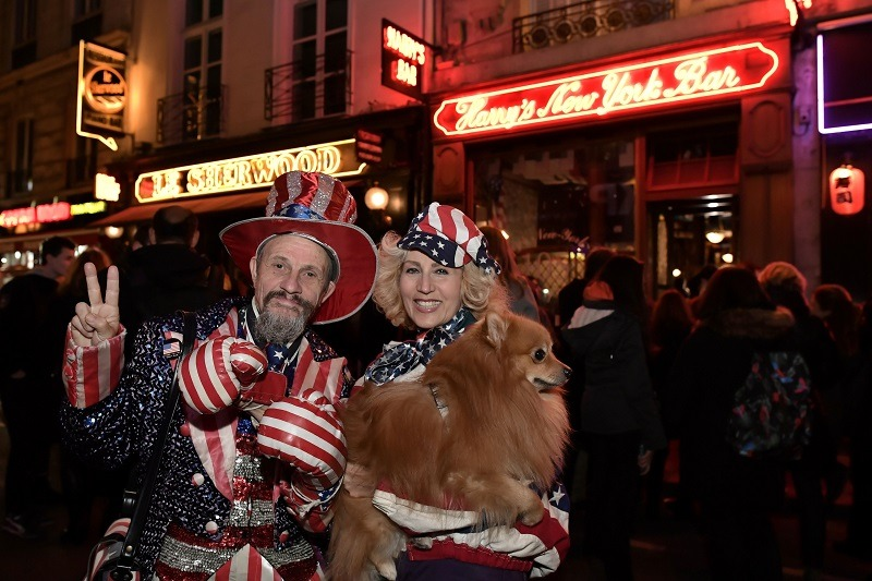 American expatriates who work abroad in France stand outside of an American bar in patriotic garb