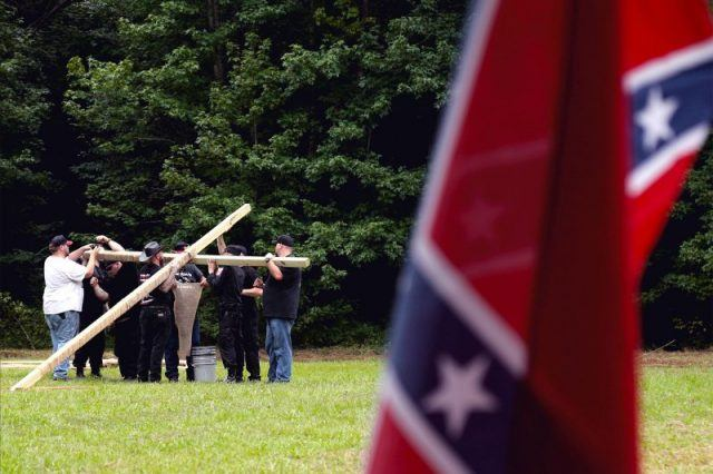 A group raises a wooden cross in front of a Confederate flag