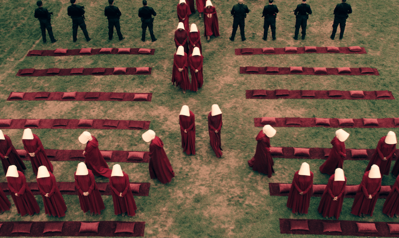 A group of women dressed in red robes with white bonnets known as Handmaids attend an outdoor gathering in Hulu's The Handmaid's Tale
