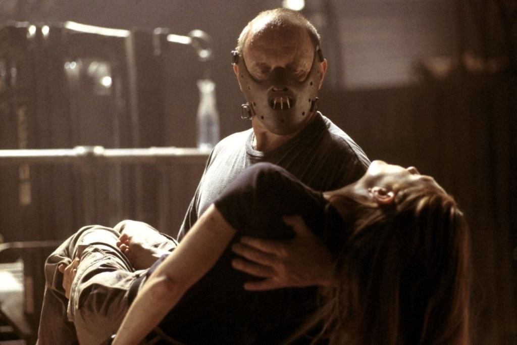 Hannibal holds an unconscious woman in his arms, wearing his trademark mask
