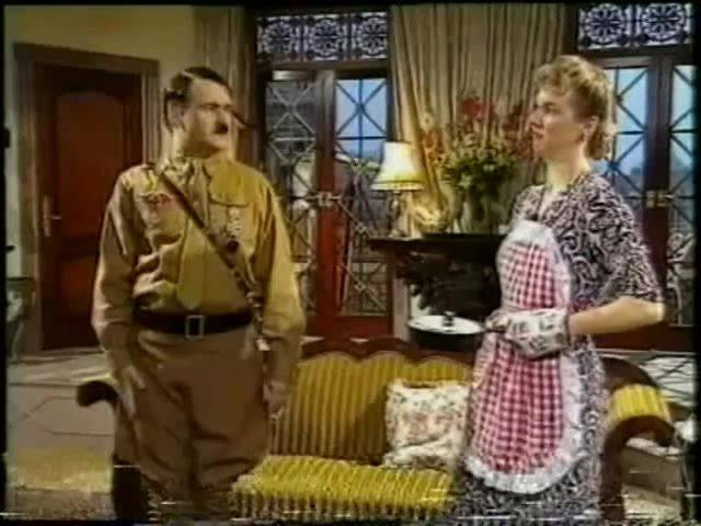 Hitler stands in a living room with his wife in an apron