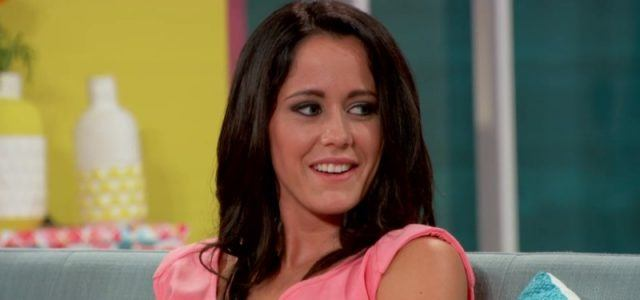Jenelle Evans looks over to her side as she sits on a couch.
