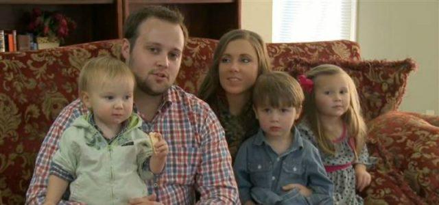 Josh Duggar and his wife are sitting on the couch holding two children on 19 and Counting.Josh Duggar and his wife are sitting on the couch holding two children on '19 and Counting'.
