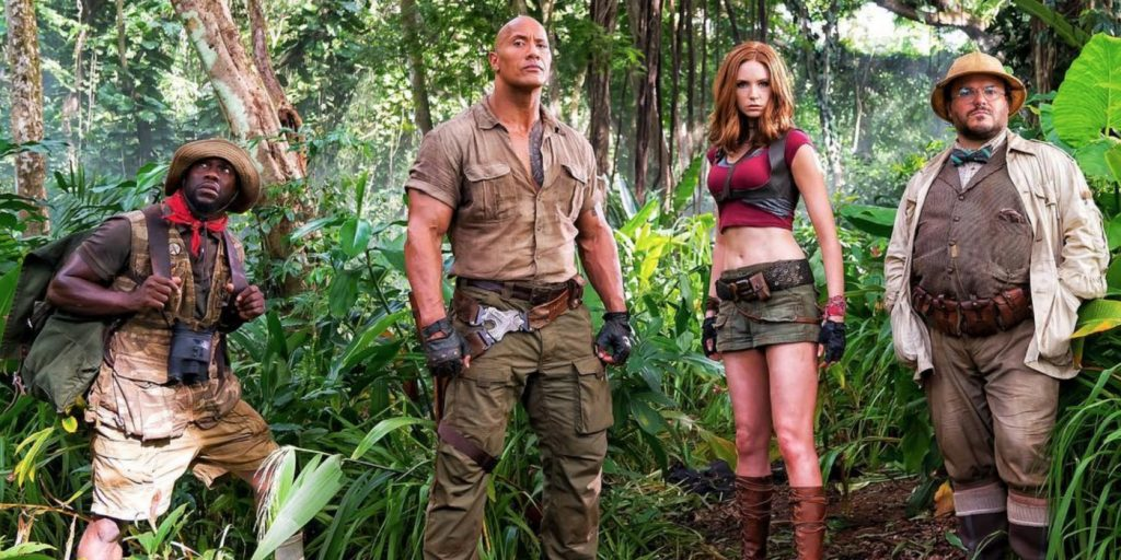 The cast of Jumanji posing in the Jungle together, clad in expeditionary gear