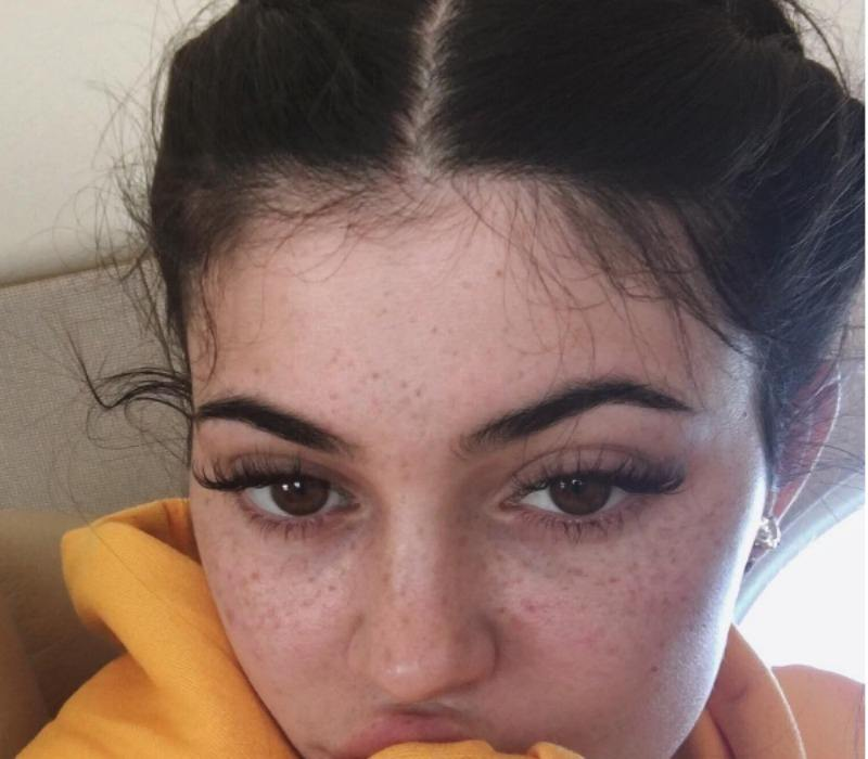 Kylie Jenner is biting into something as she poses for a selfie.
