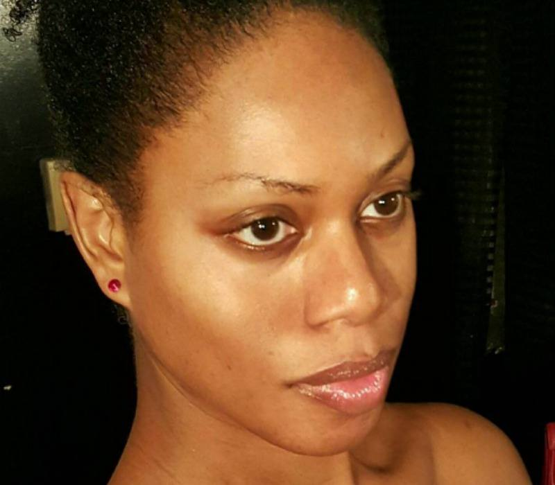 Laverne Cox has no makeup on and her hair is up in a bun.