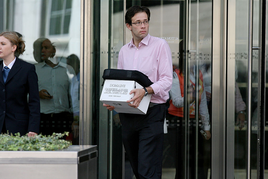 A man carrying a box leaves a financial firm