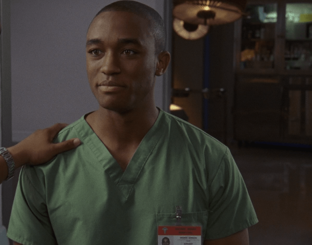 Lee Thompson young wearing surgeons scrubs with a hand on his shoulder