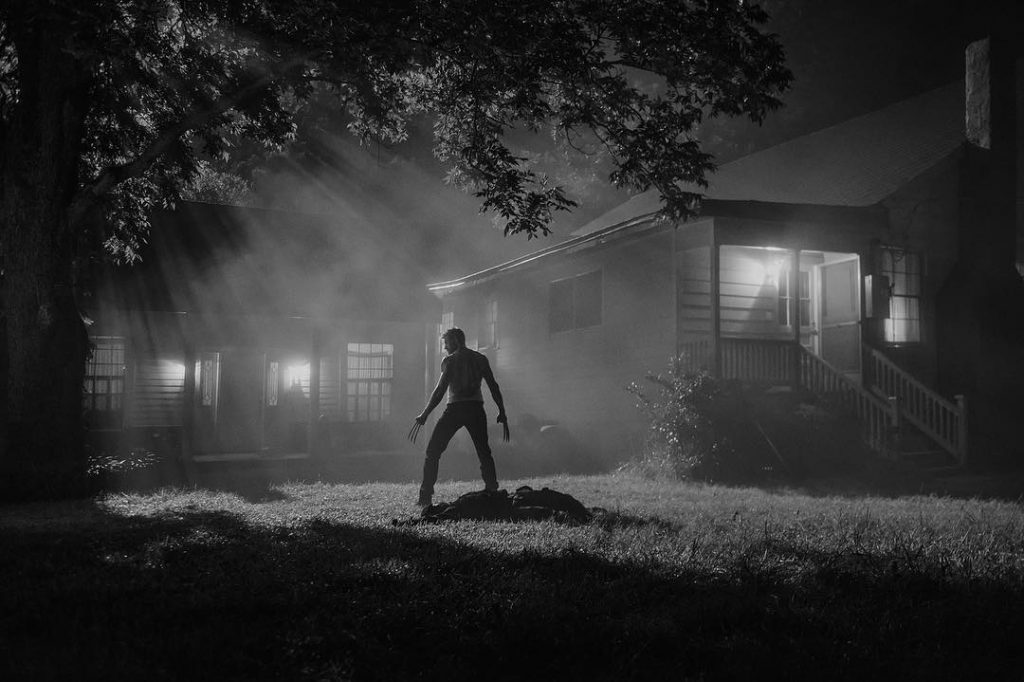Hugh Jackman's Wolverine stands outside of a house with his claws out in a scene from Logan