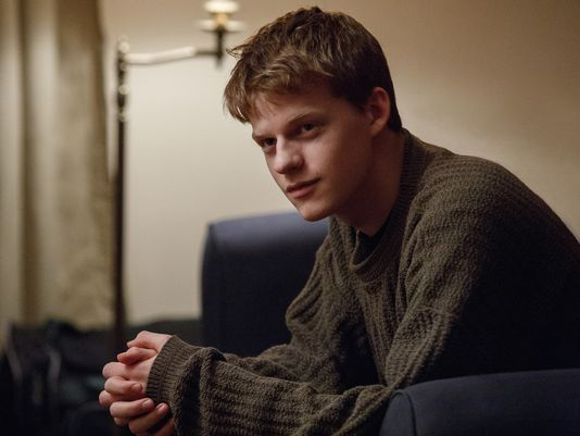 Patrick sits on the couch with his hands folded in a scene from 'Manchester By the Sea.'