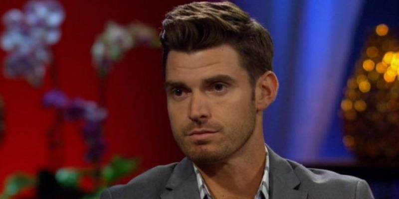 Luke Pell is wearing a grey suit and looks serious.