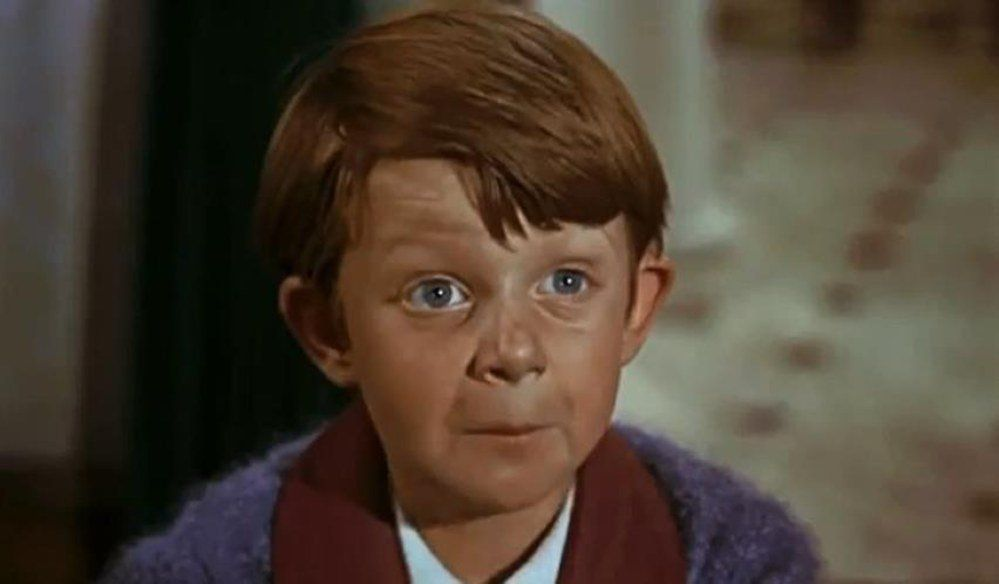Matthew Garber looks up at the camera, wearing a blue robe in Mary Poppins