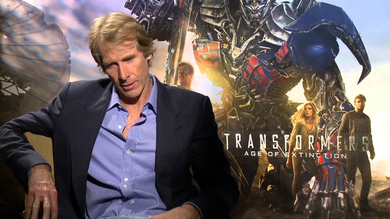 Michael Bay in an interview, sitting in front of a Transformers poster background