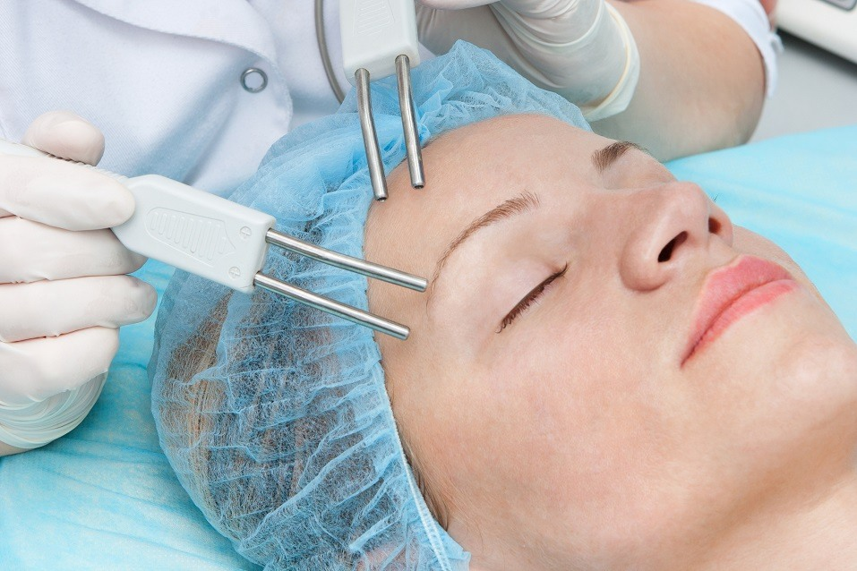 woman having microcurrent therapy by cosmetologist