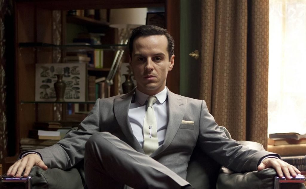 Moriarty, with his legs crossed and a grey suit, sitting and looking into the camera