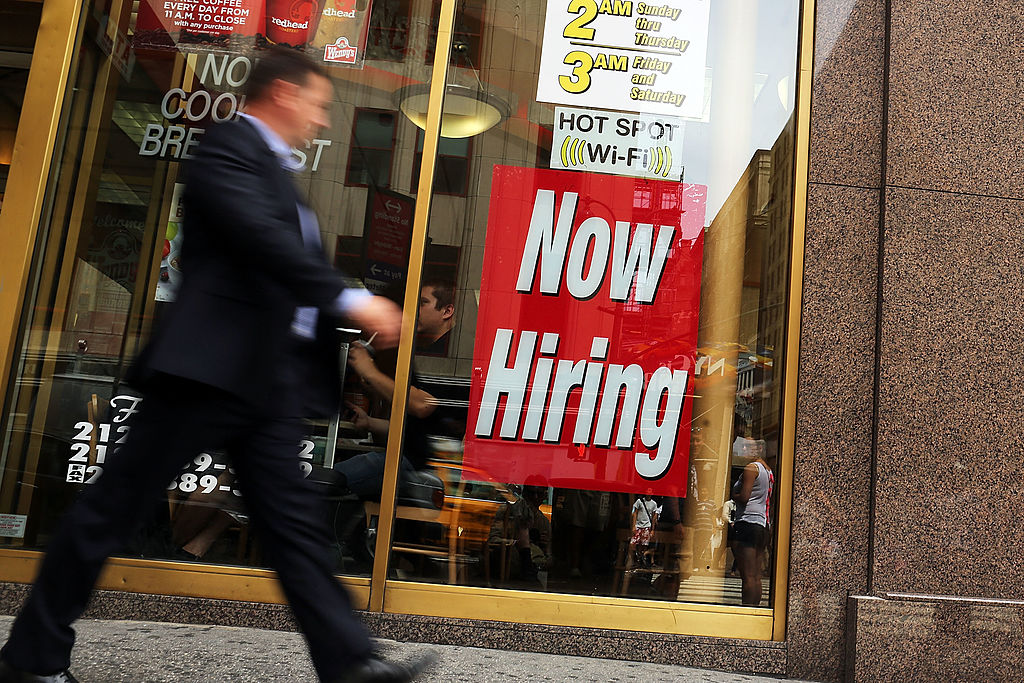 a man walks by a now hiring sign