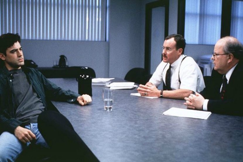 Peter Gibbons sits in an interview with consultants in the movie Office Space