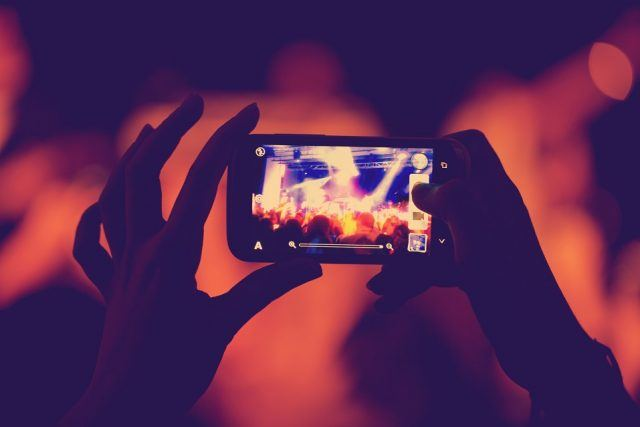 A woman captures a concert on her smartphone
